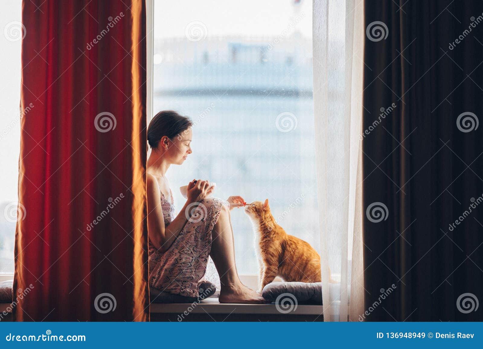 Młoda dziewczyna z czerwonym kotem w domu