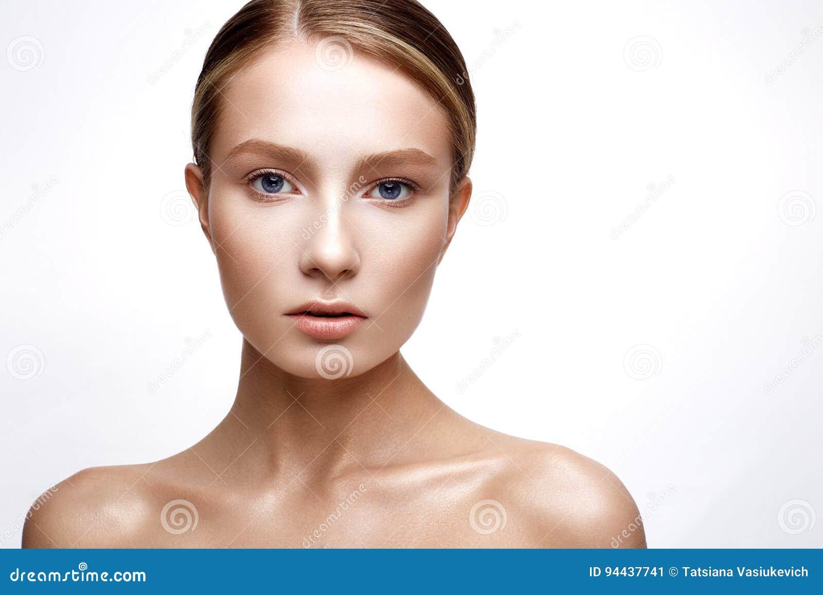 Młoda dziewczyna z perfect olśniewającą skórą Piękny model z podstawy i nagiej postaci makeup Czyści skórę Biały odosobniony tło