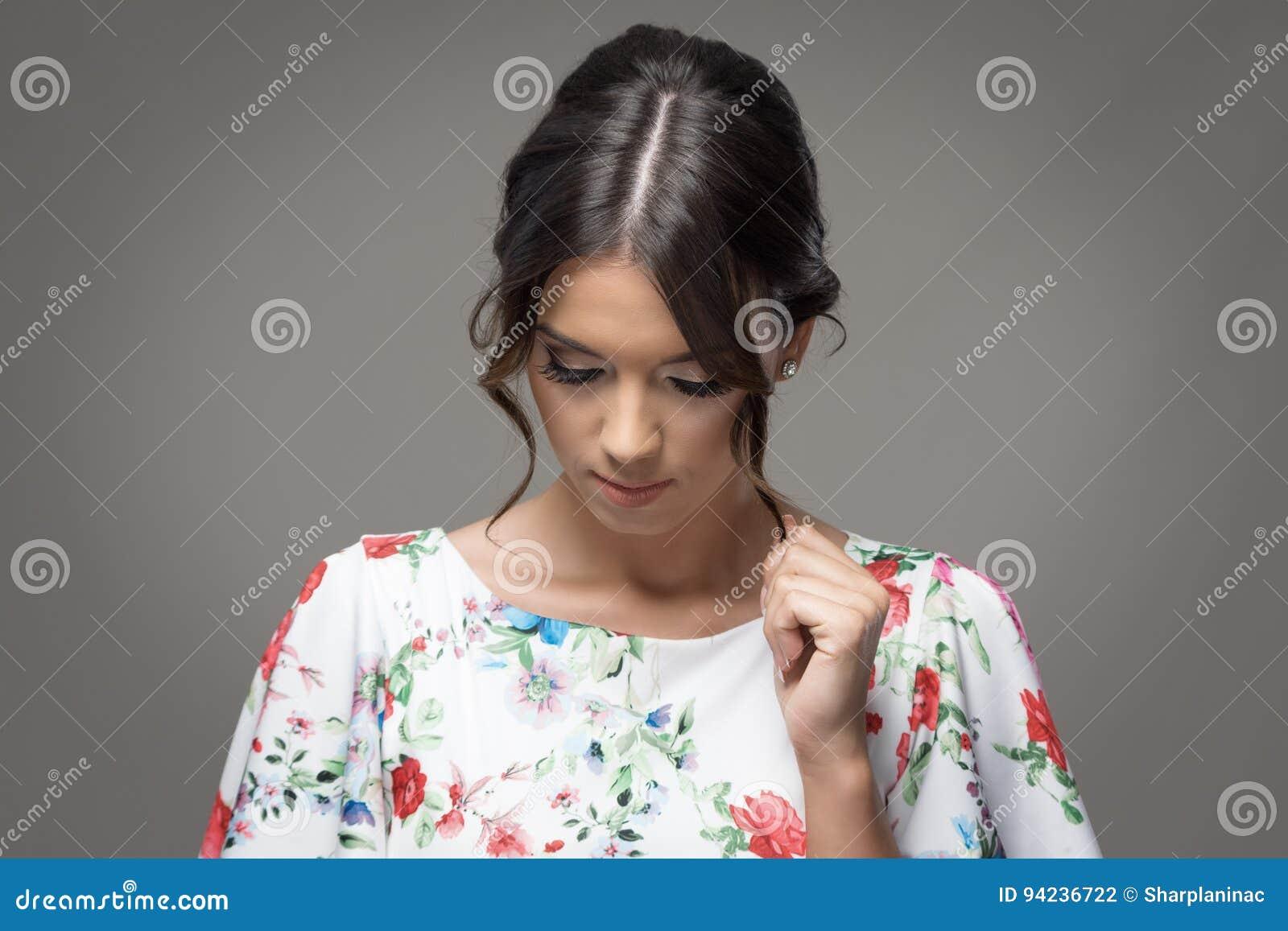 Młoda elegancka kobieta patrzeje w dół z babeczki fryzury wzruszającym włosianym kędziorkiem
