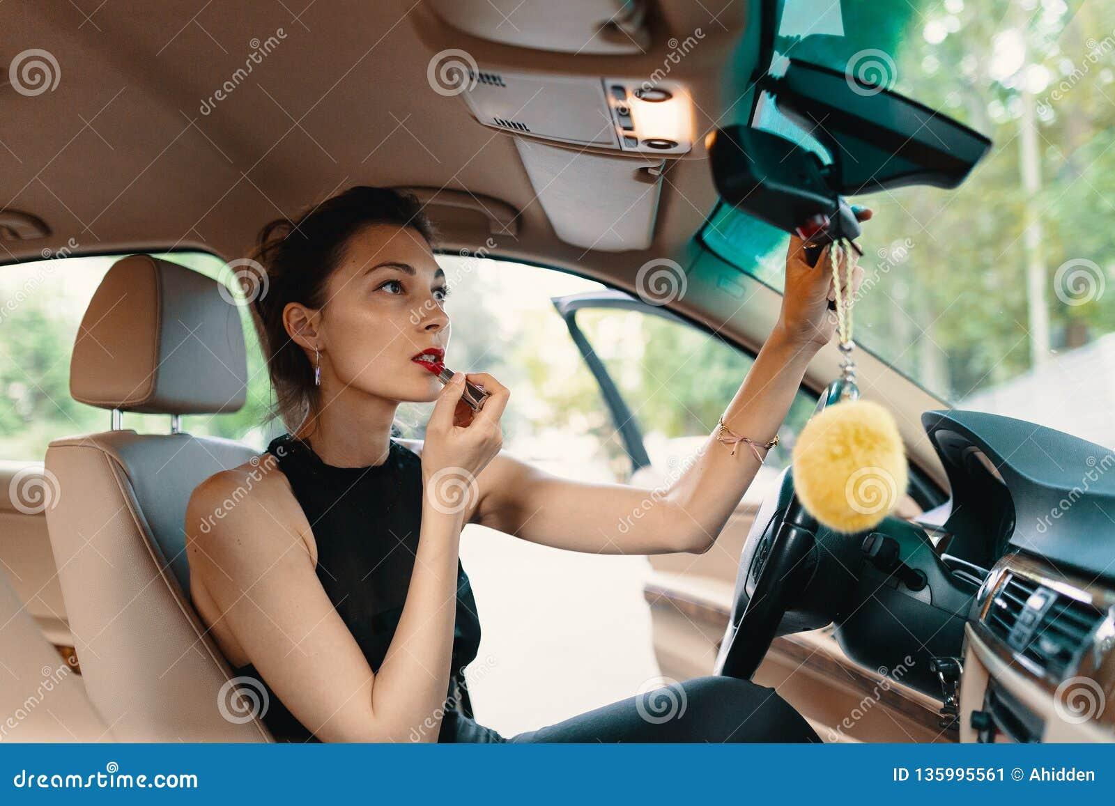 Młoda elegancka kobieta patrzeje w samochodowym widoku lustrze podczas gdy stosować makeup, pomadka na wargach