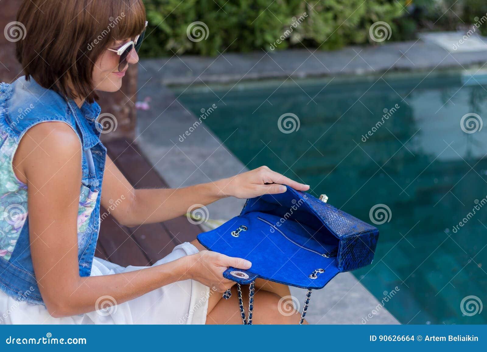 Młoda elegancka kobieta w modnym stroju z snakeskin pytonu luksusową torbą w rękach Kobieta z torebką blisko dopłynięcia