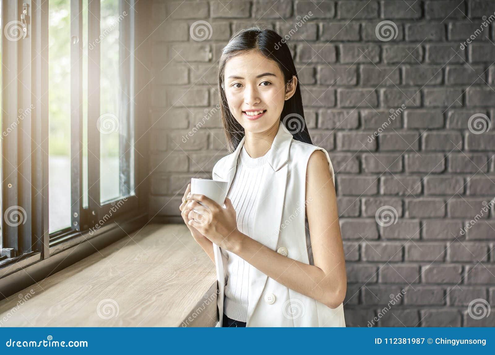 Młoda i ładna Asia kobieta z filiżanka kawy uśmiechem w kawiarni