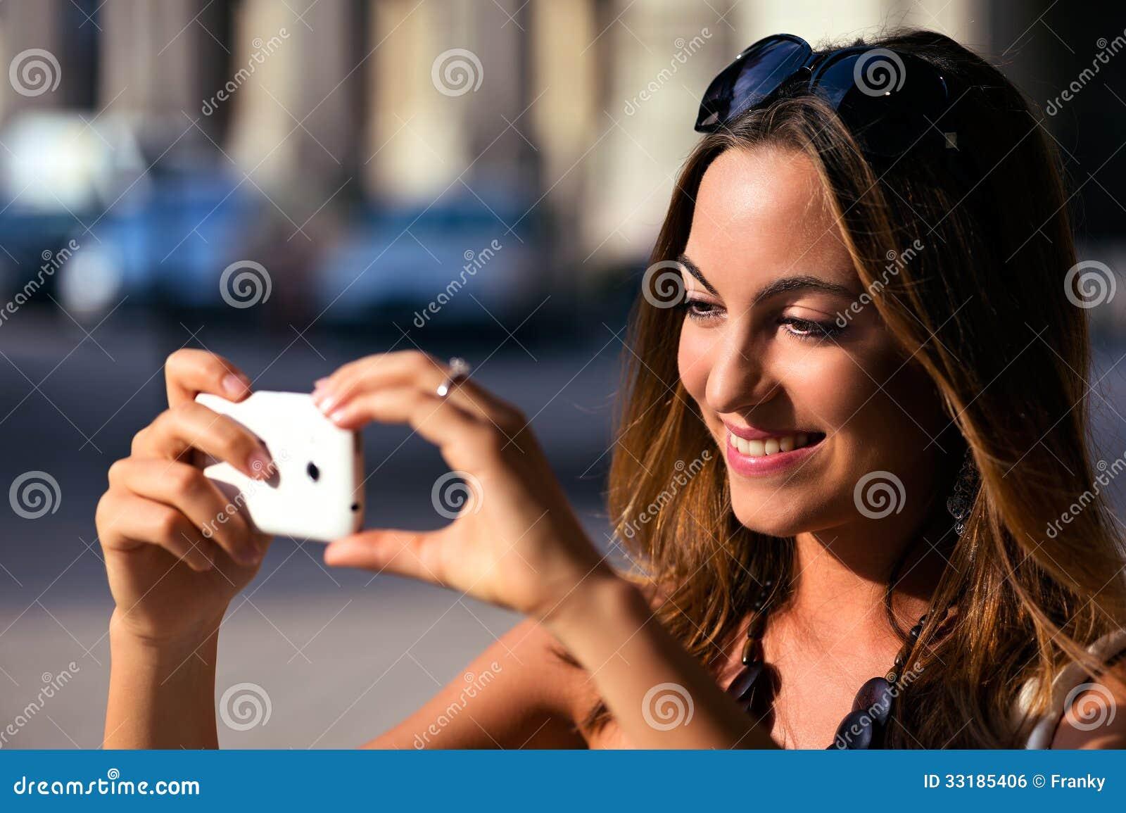 Młoda i ładna kobieta bierze fotografię z jej smartphone