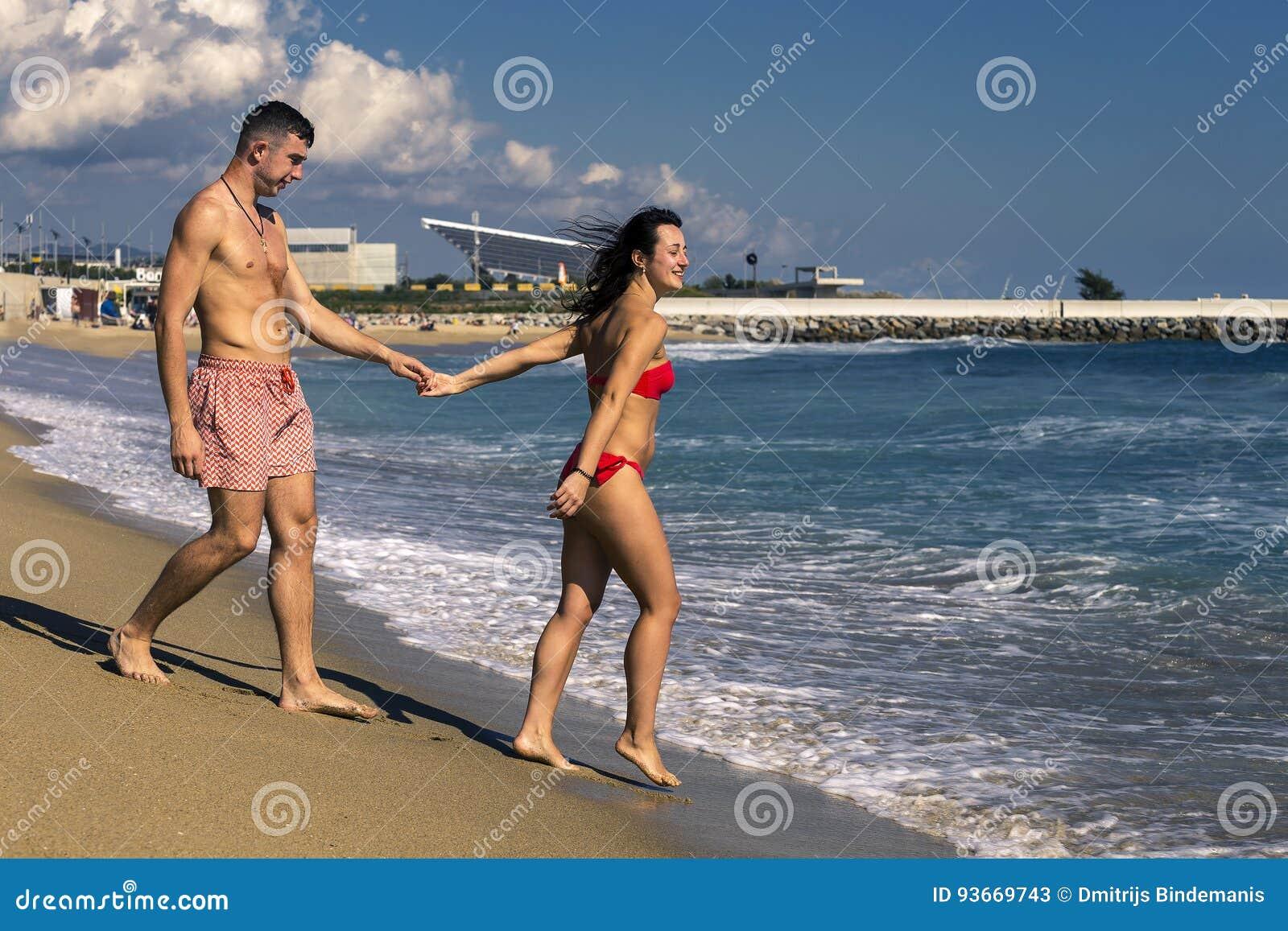 Młoda i piękna para stoi na piaskowatej plaży