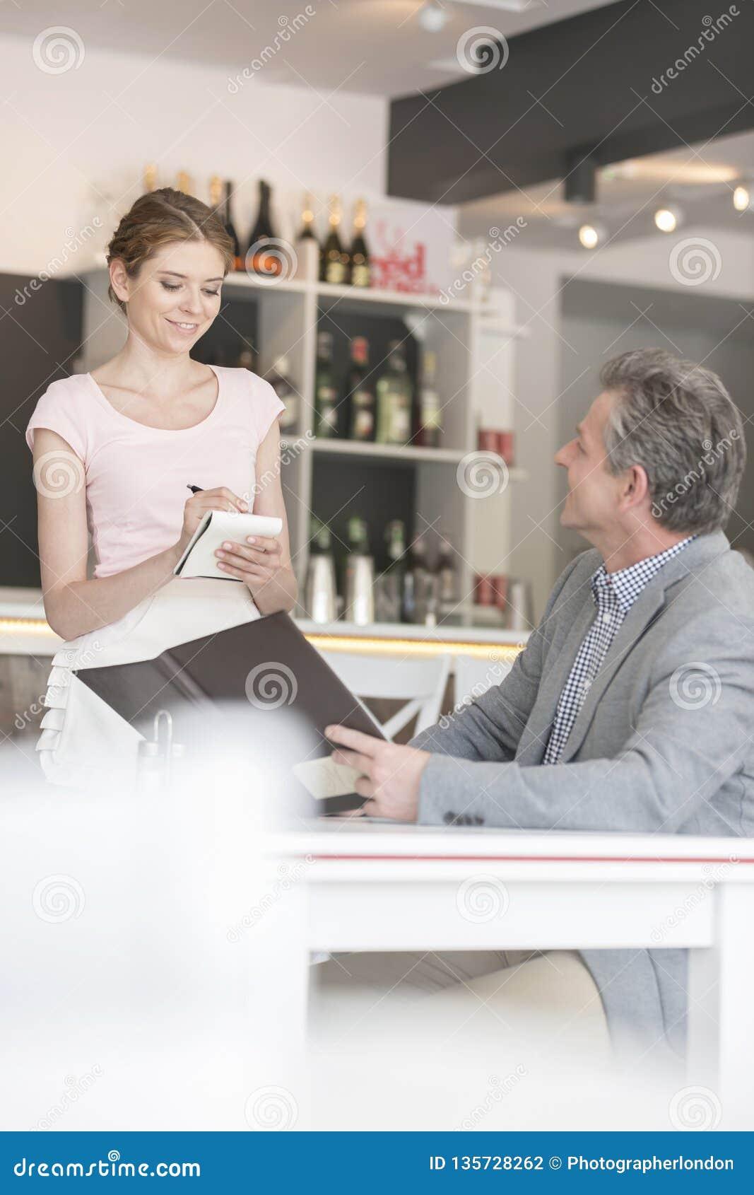 Młoda kelnerka bierze rozkaz od dojrzałego klienta przy restauracją