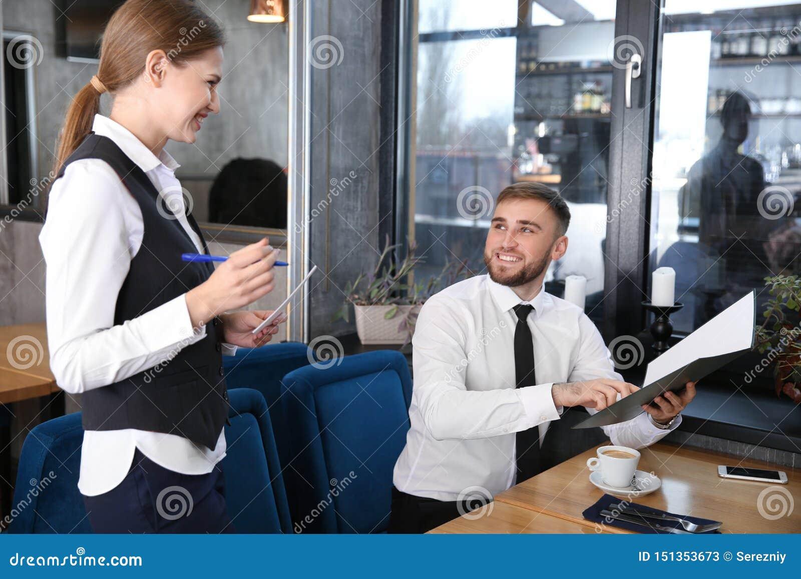 Młoda kelnerka bierze rozkaz od mężczyzny w restauracji