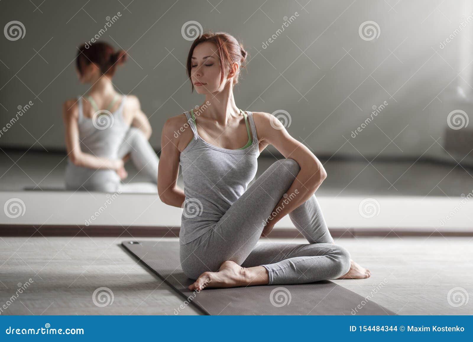 Młoda kobieta ćwiczy joga w lekkim pokoju robi pięknemu asana ćwiczy