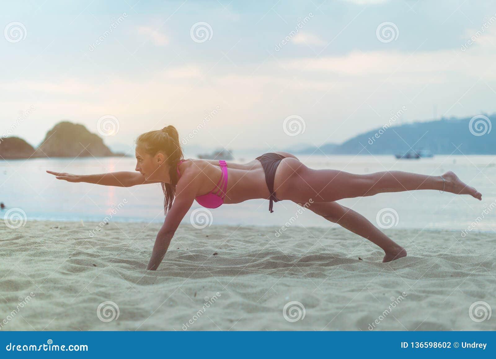 Młoda kobieta ćwiczy na plażowym rozciąganiu ona podczas zmierzchu przy morzem w swimsuit nogi Sprawności fizycznej dziewczyna ro