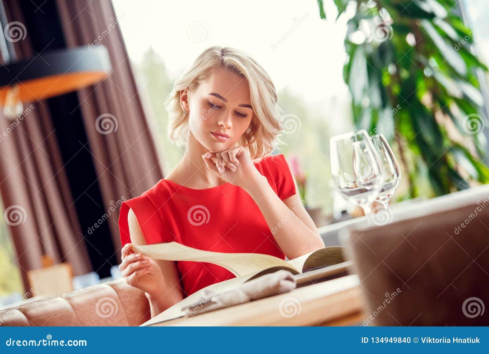 Młoda kobieta łomota w restauracyjnym siedzącym patrzeje menu rozważnym