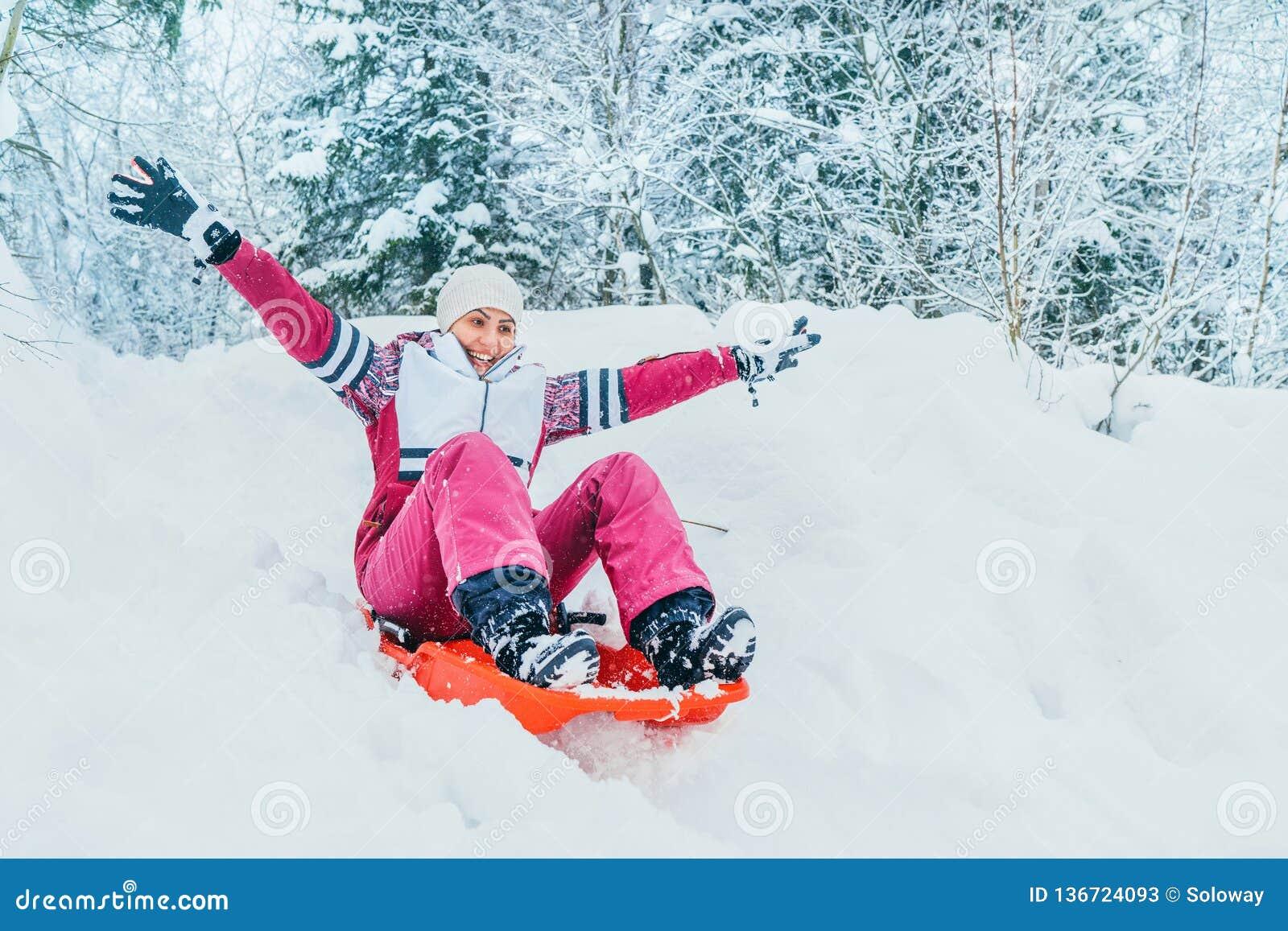 Młoda kobieta ślizga się puszek od śnieżnego skłonu obsiadania w jeden obruszeniu Zim aktywność pojęcia wizerunek
