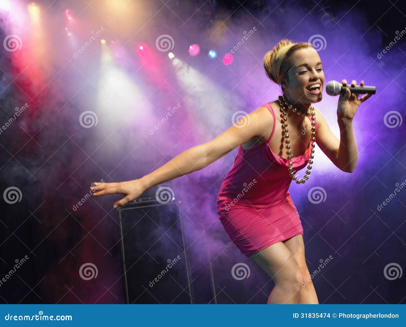 Młoda Kobieta śpiew W mikrofon