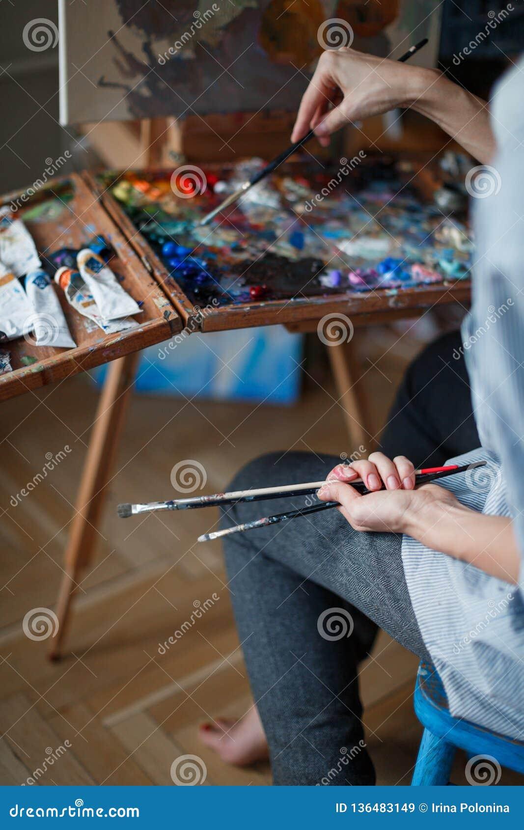 Młoda kobieta artysta maluje obraz olejnego na sztaludze