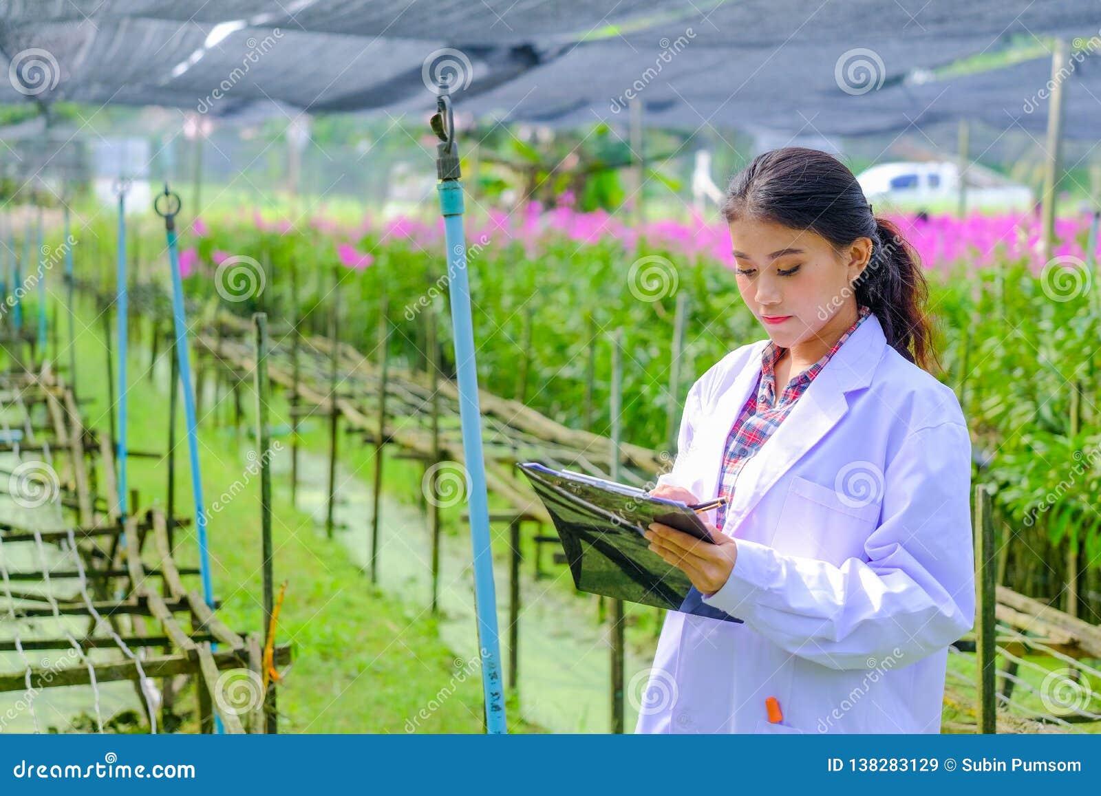 Młoda kobieta badacz w białej sukni i bada ogród przed zasadzać nowej orchidei