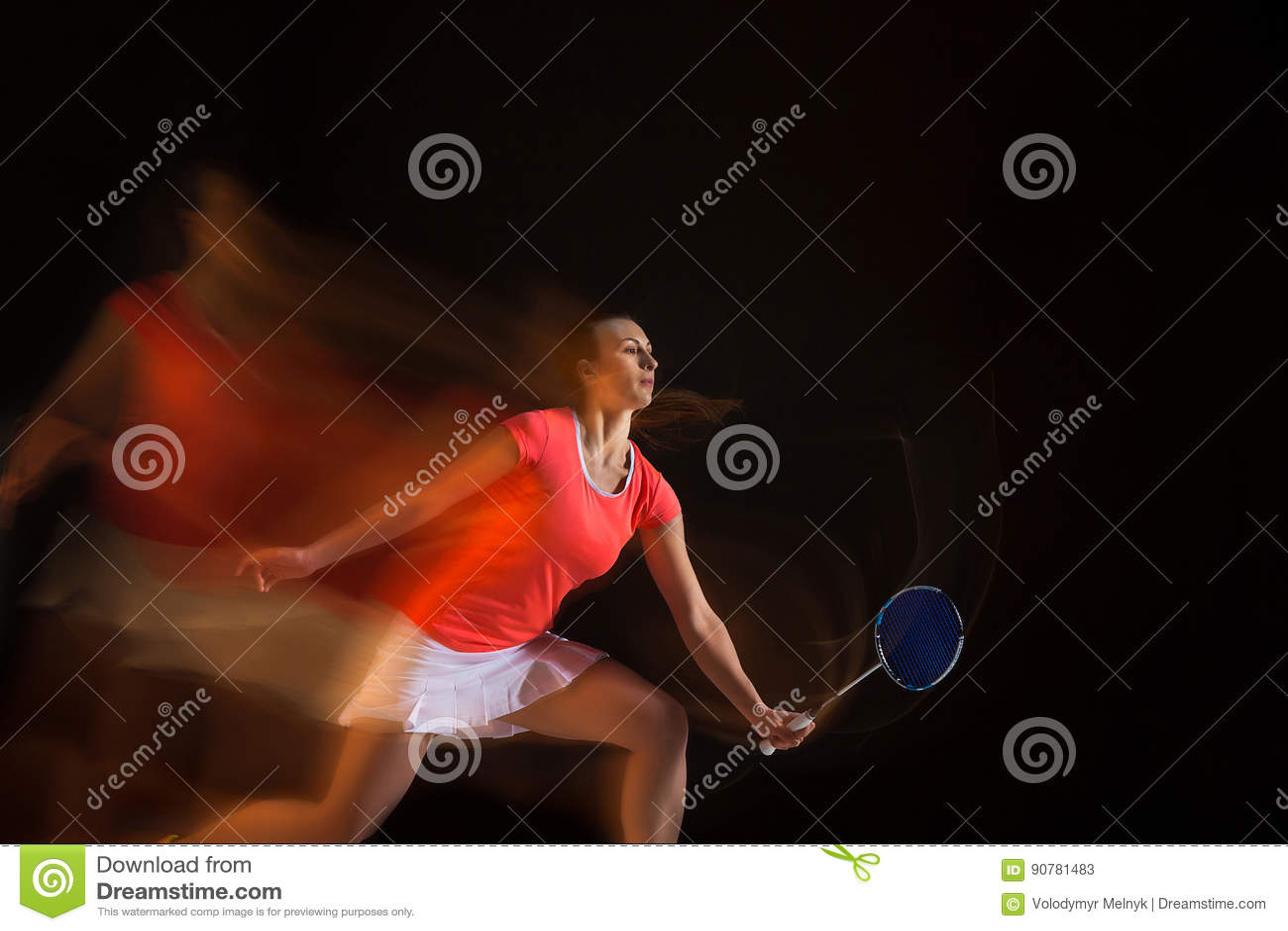Młoda kobieta bawić się badminton nad czarnym tłem