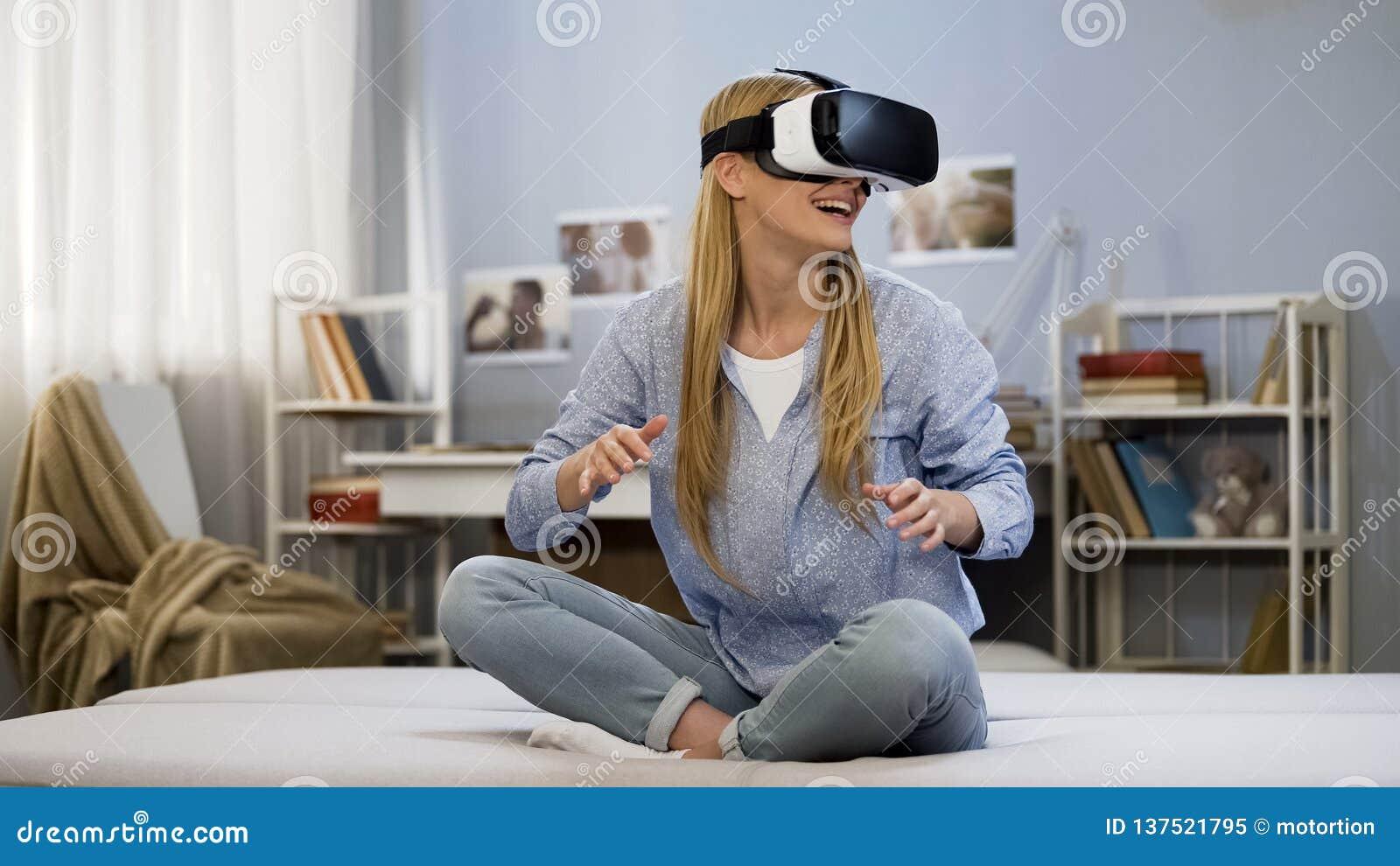 Młoda kobieta bawić się gry używać vr słuchawki szkła w domu, zadziwiający doświadczenie