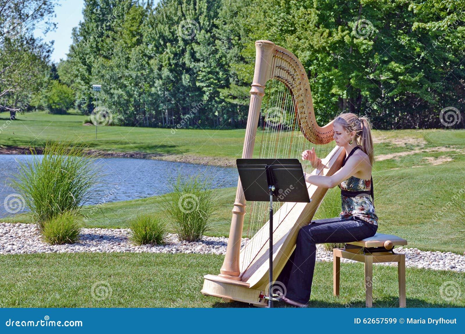 Młoda kobieta bawić się harfę stawem