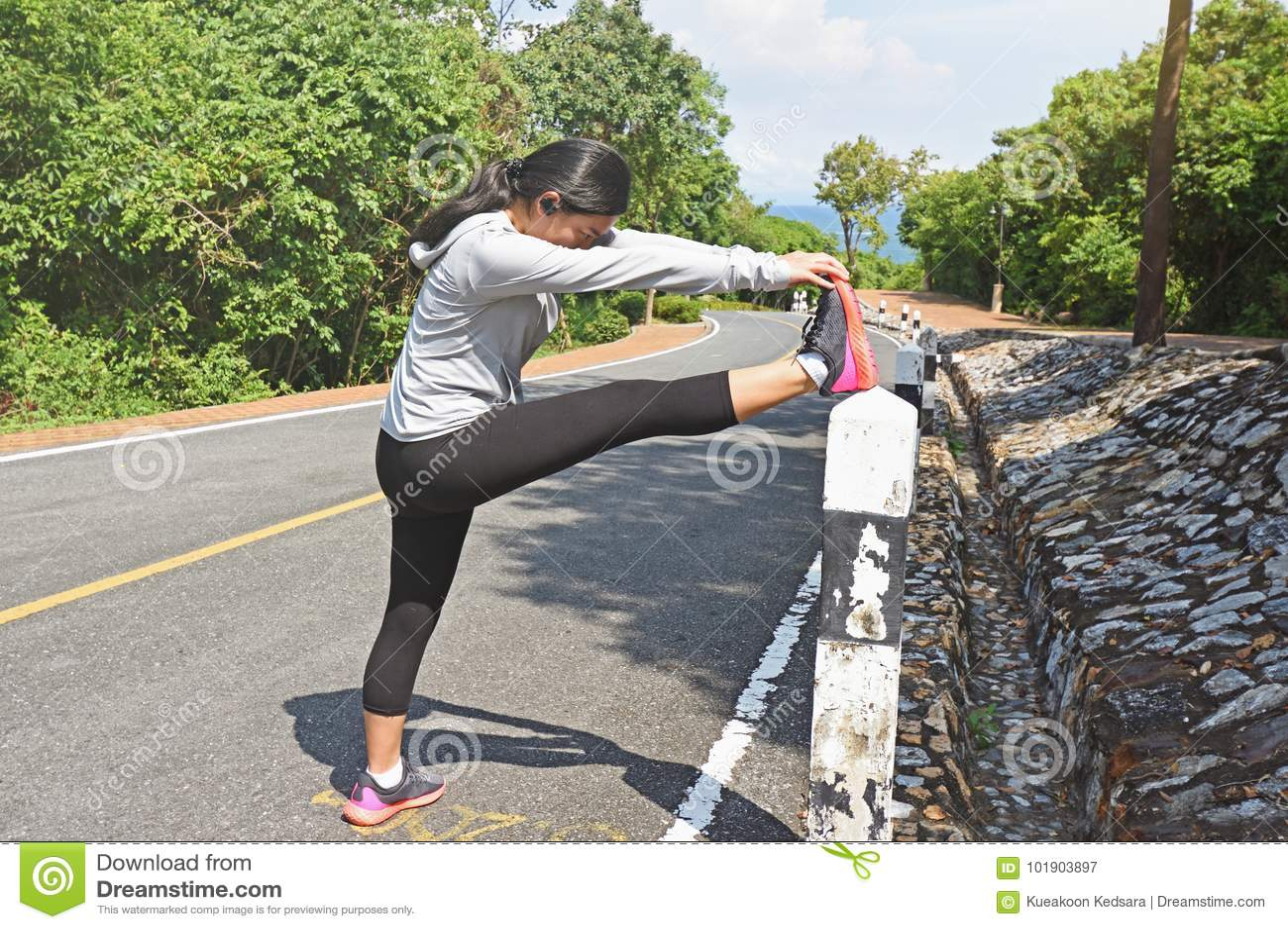Młoda kobieta biegacza rozciągania nogi przed biegać plenerowy