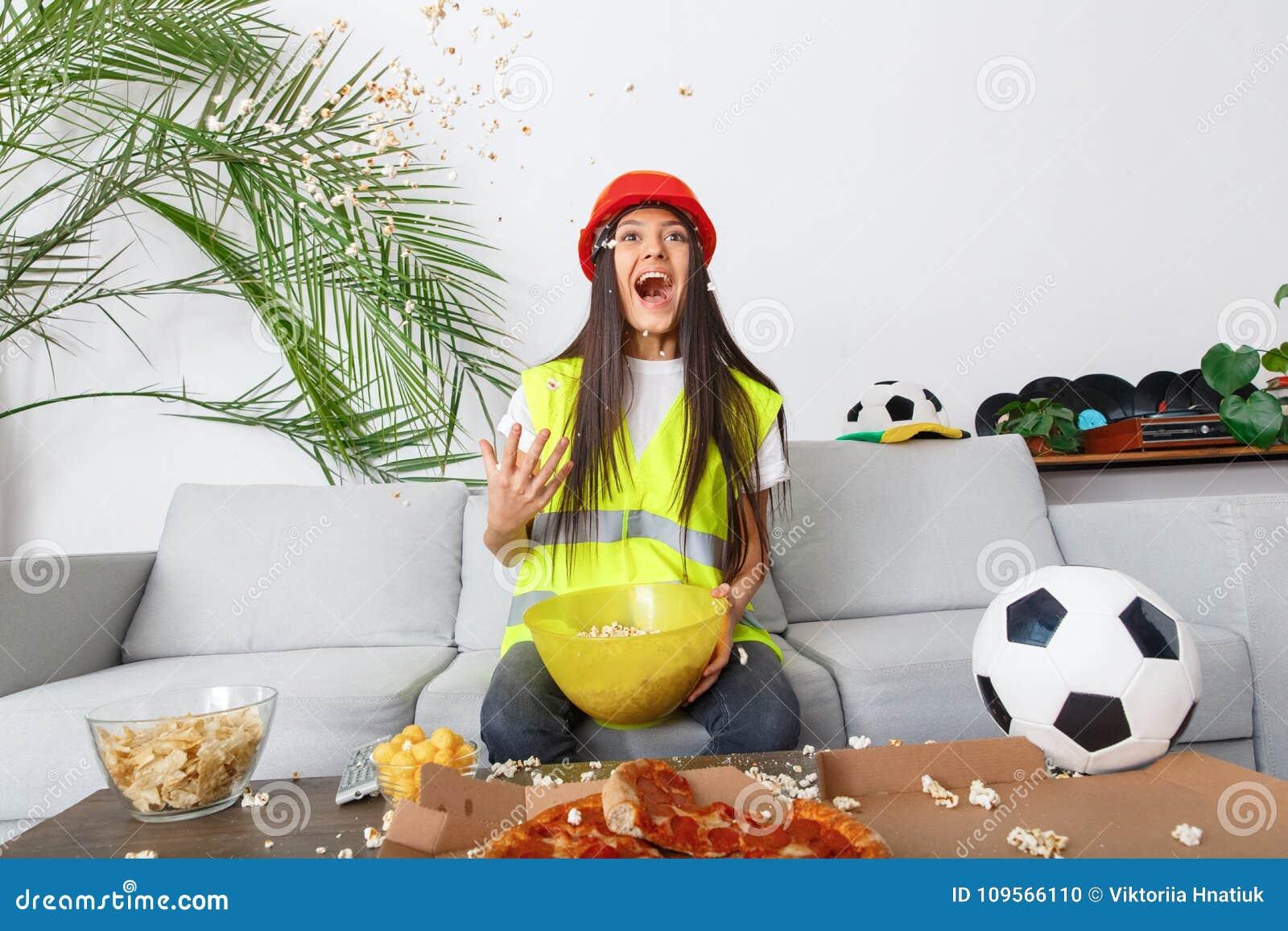 Młoda kobieta budowniczego wielbiciela sportu dopatrywania dopasowania miotania popkorn