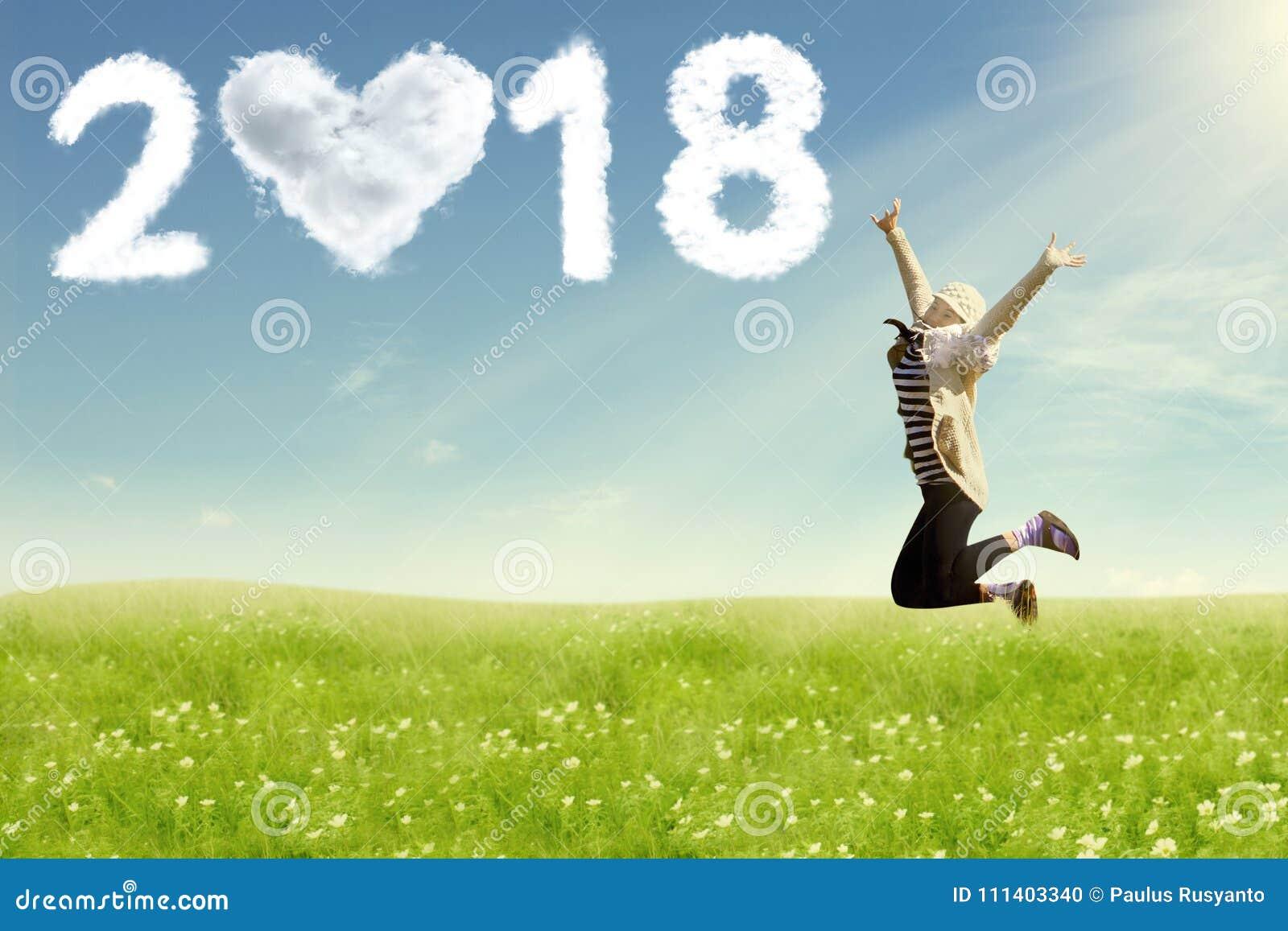 Młoda kobieta cieszy się nowego roku doskakiwanie na polu