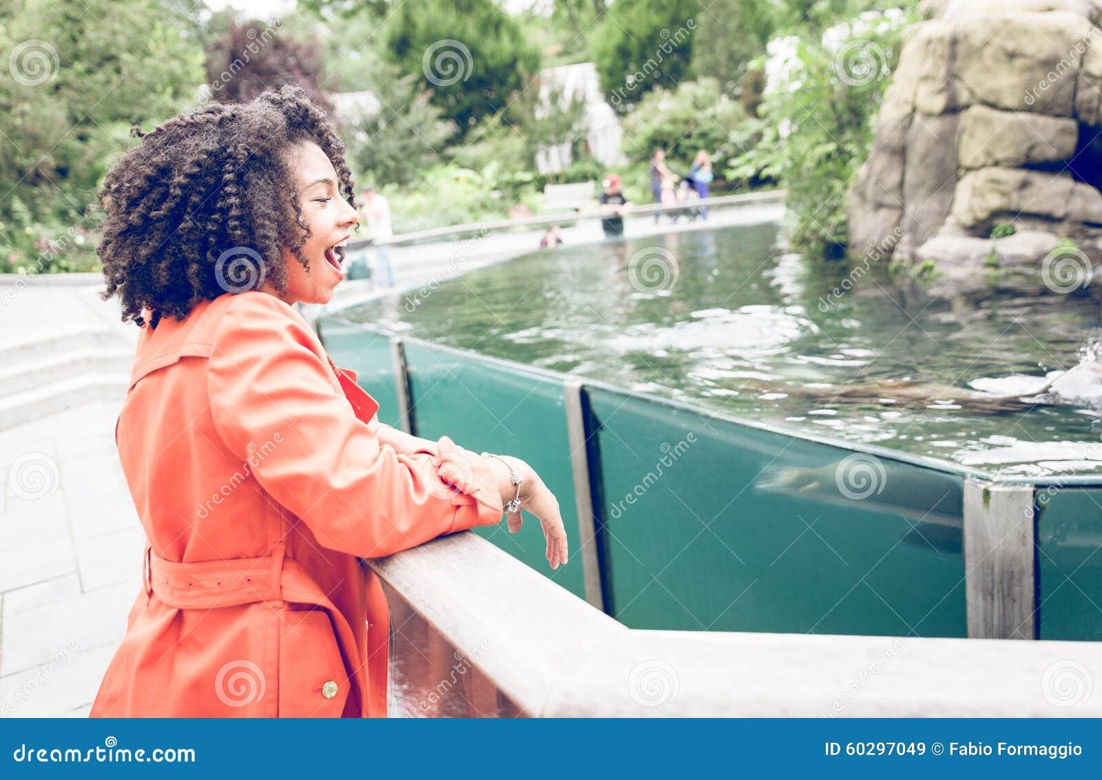 Młoda kobieta cieszy się przedstawienie przy zoo