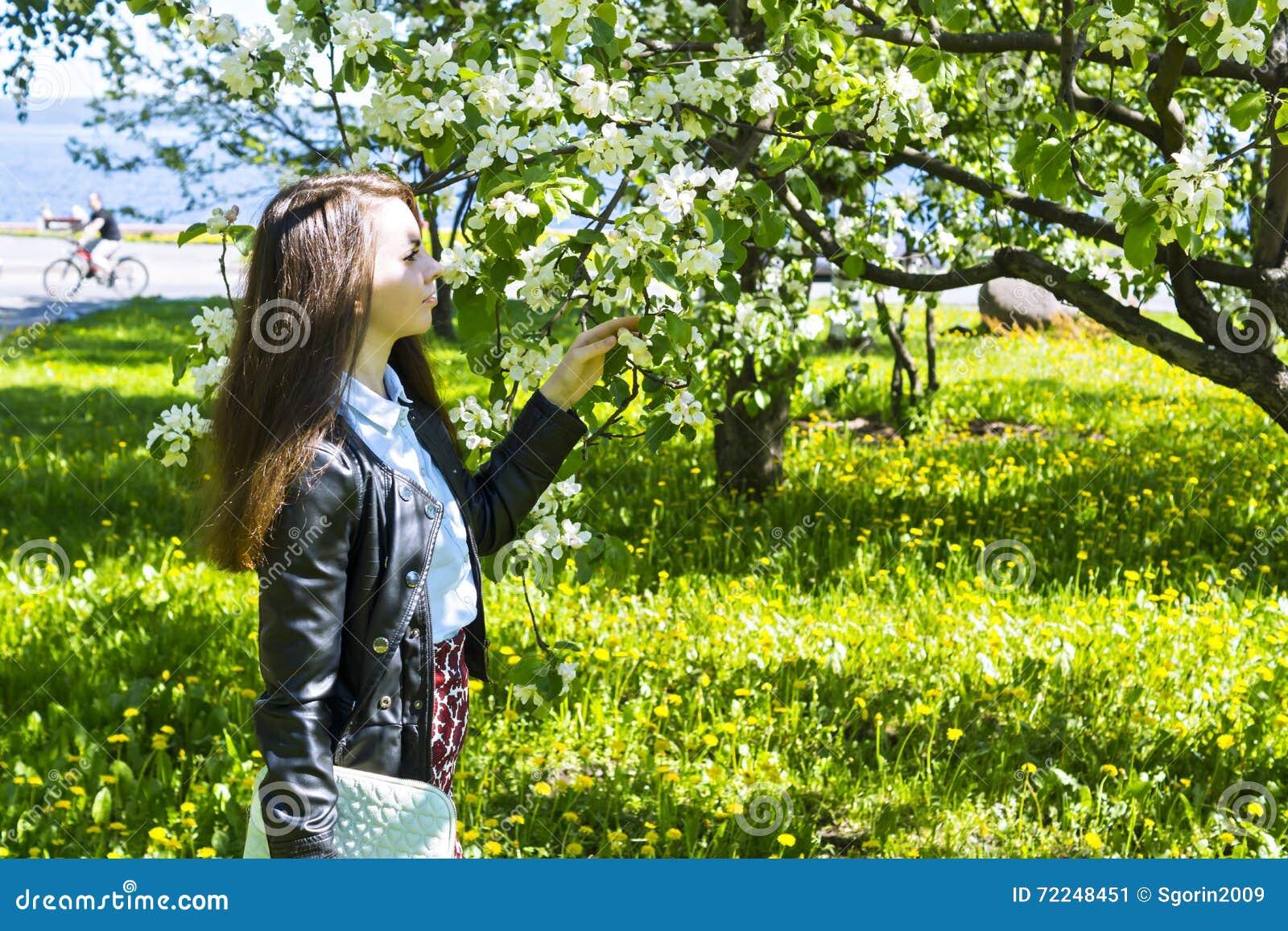 Młoda kobieta cieszy się woń jabłoń