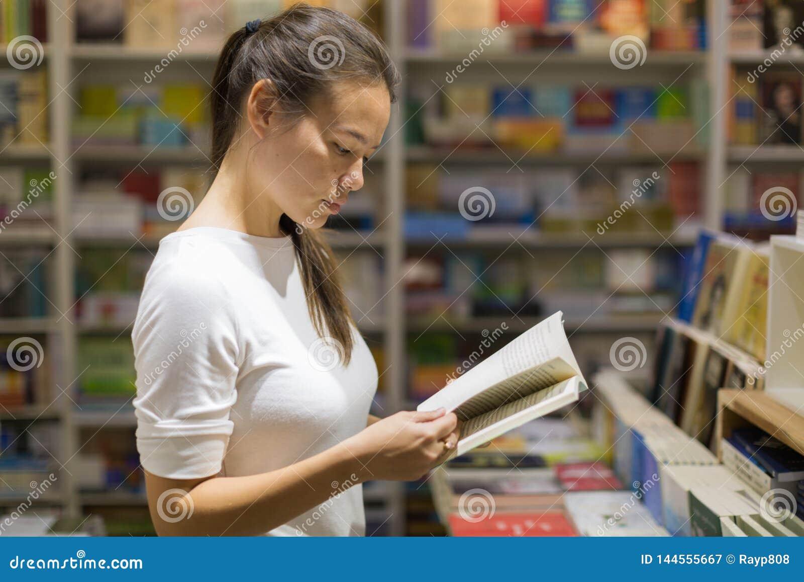 Młoda kobieta czyta książkę w bibliotece