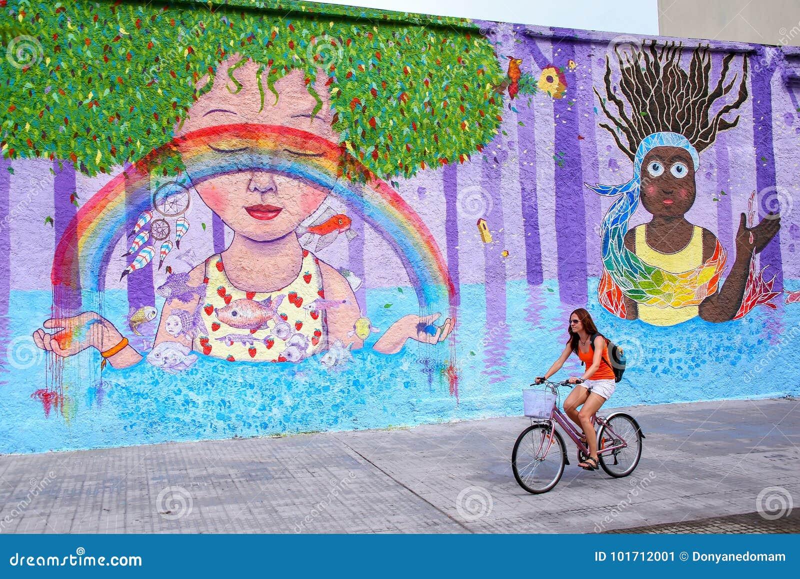 Młoda kobieta jechać na rowerze wzdłuż kolorowej ściany w Montevideo, Urugwaj