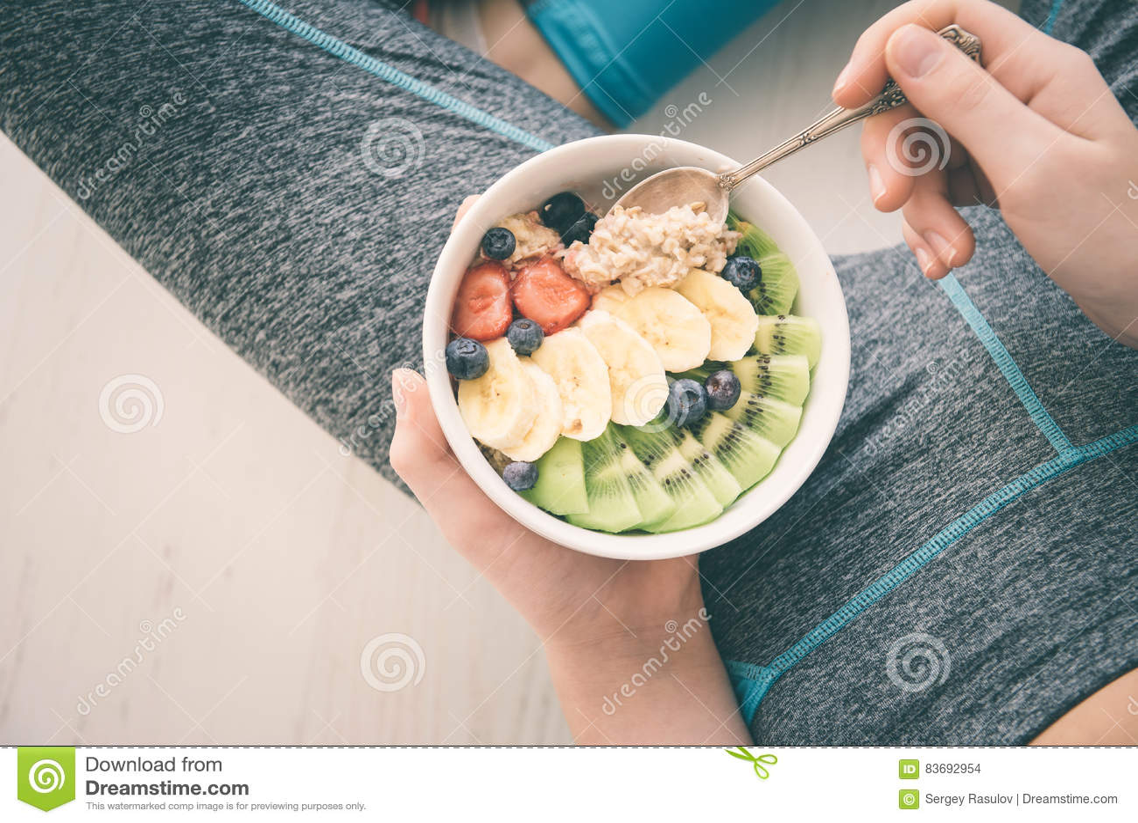 Młoda kobieta jest odpoczynkowa i jedząca zdrowego oatmeal po treningu