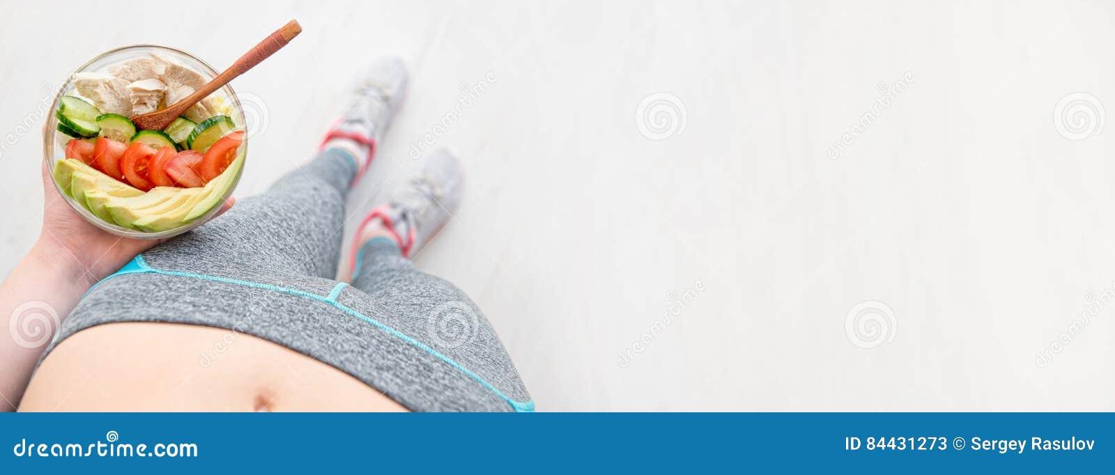 Młoda kobieta jest odpoczynkowa i jedząca zdrowej sałatki po treningu