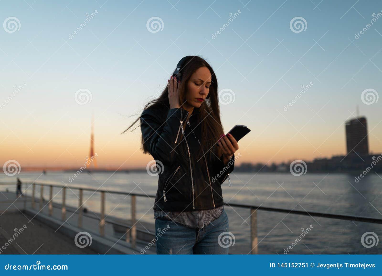 Młoda kobieta jest ubranym skórzaną kurtkę i cajgi przy zmierzchem blisko słucha muzyka w zamkniętych hełmofonach przez je