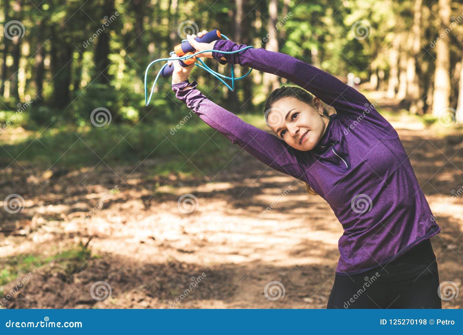 Młoda kobieta jogging ćwiczenia w pogodnym lesie i robi