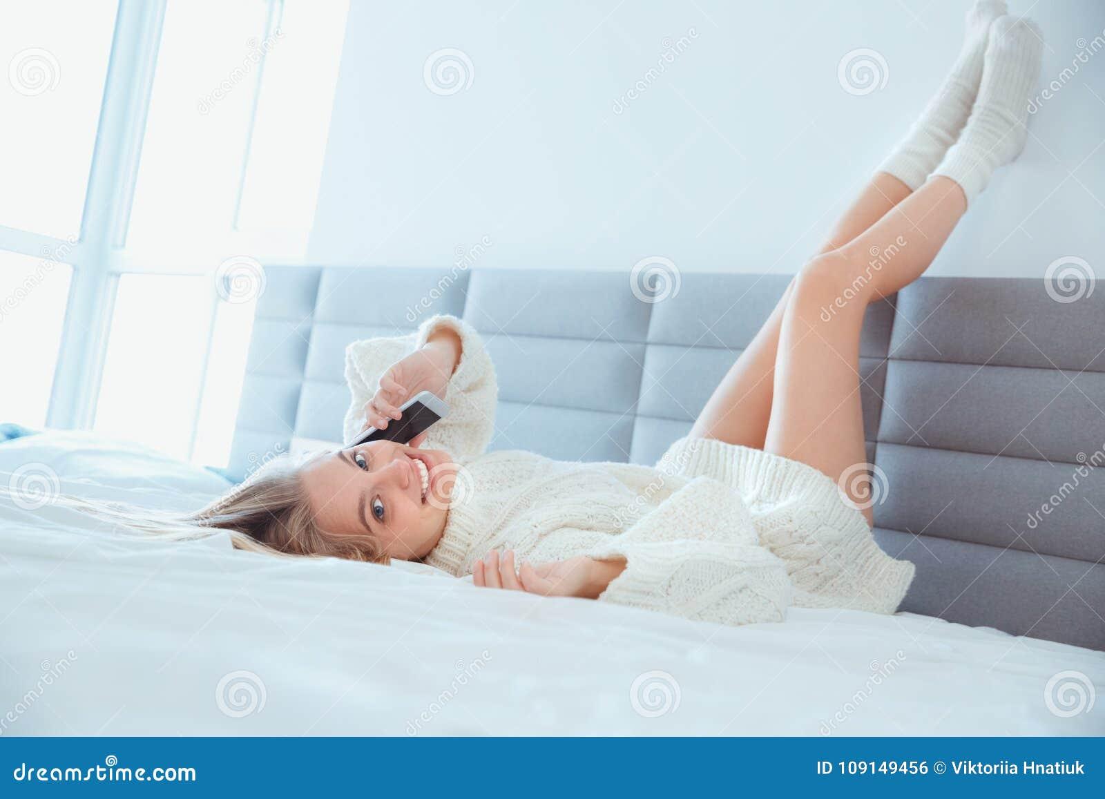 Młoda kobieta kłaść w domu iść na piechotę up na ścianie w łóżkowej jest ubranym pulower rozmowy telefonicza przyglądającej kamer