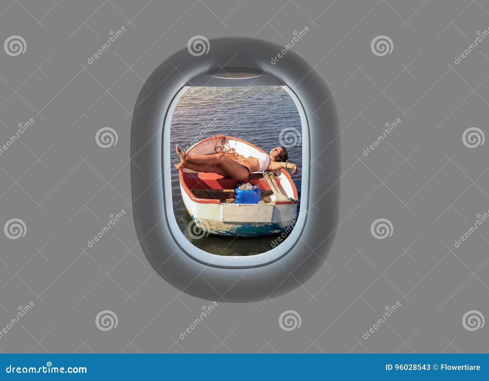 Młoda kobieta kłama w drewnianej łodzi na zmierzchu w płaskim okno nad samolotowy komarnicy ziemi widok na ocean okno