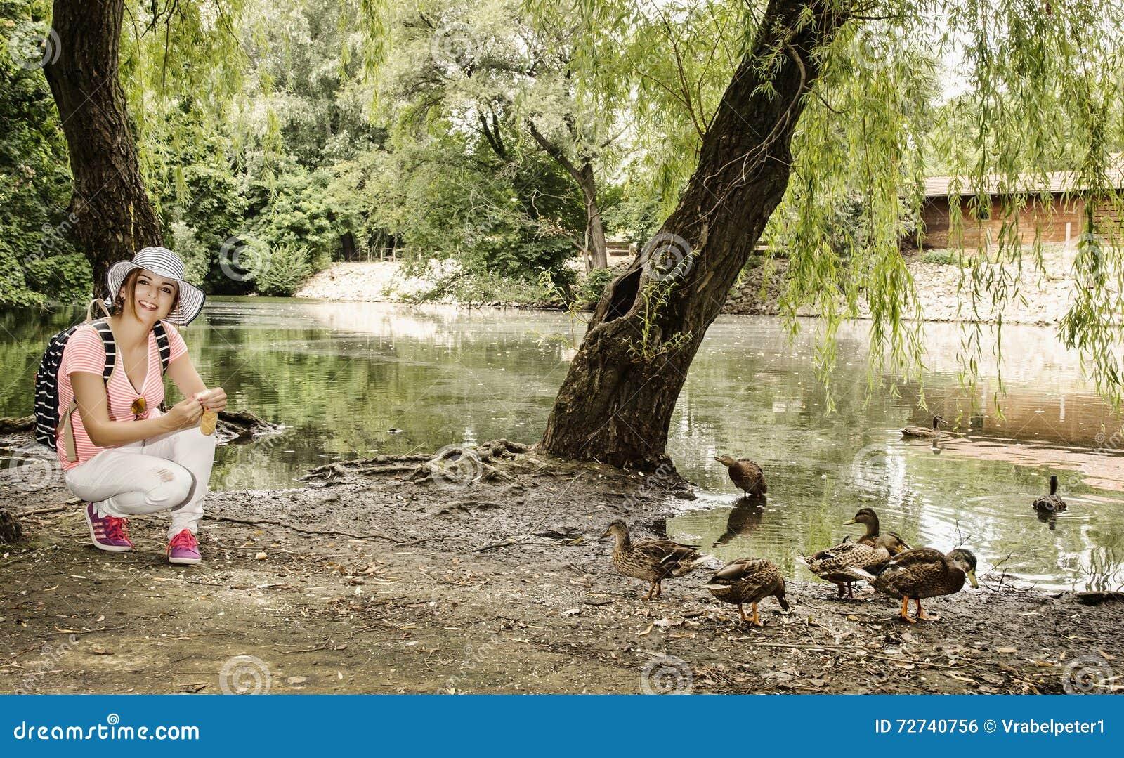 Młoda kobieta karmi grupy kaczka w miasto parku