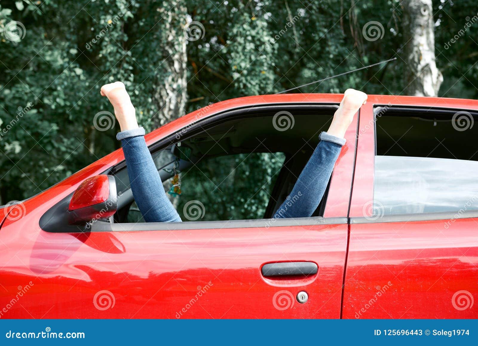 Młoda kobieta kierowca odpoczywa w czerwonym samochodzie, stawia jej cieki na samochodowym okno, szczęśliwy podróży pojęcie