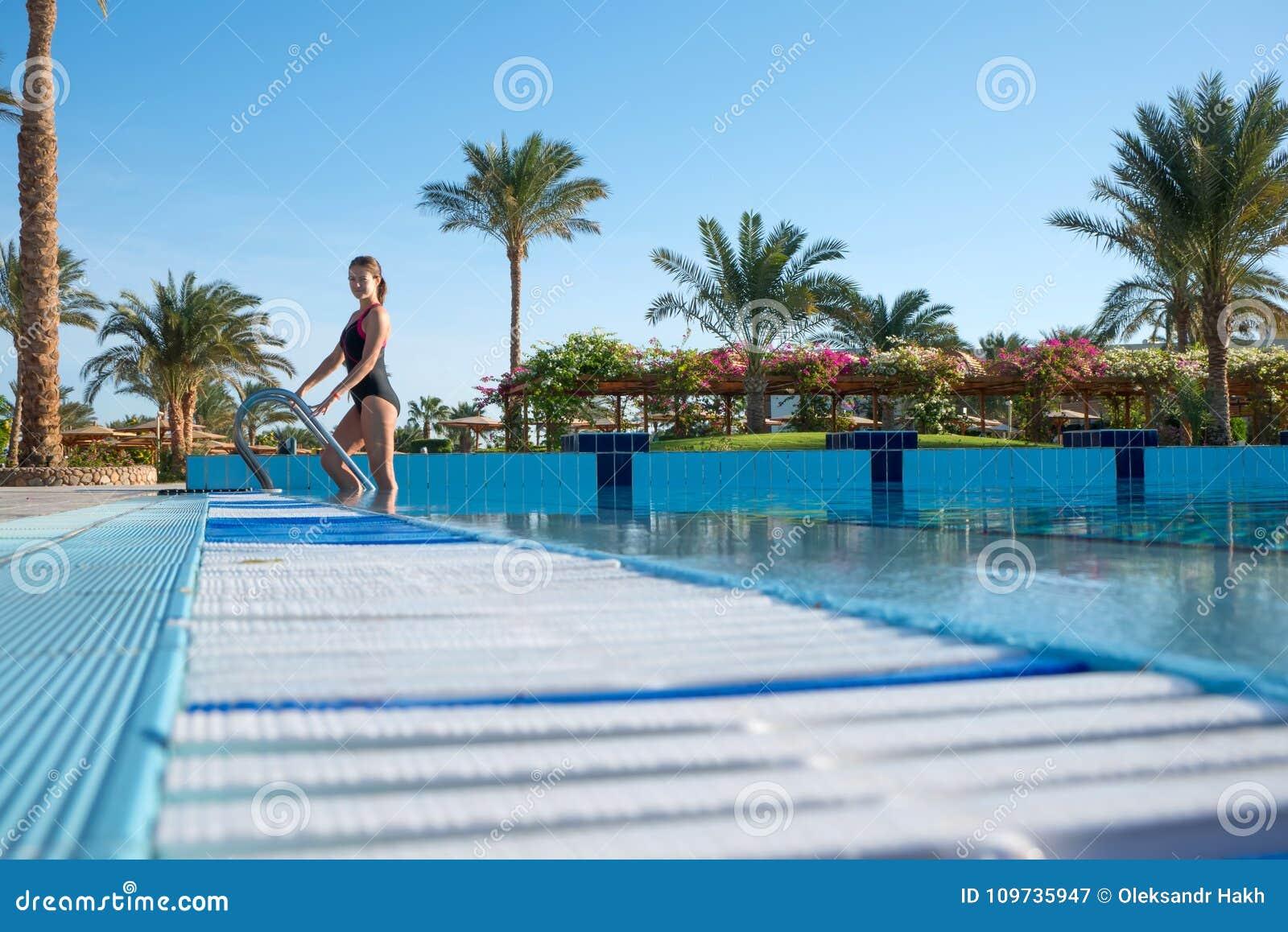 Młoda kobieta komes z sporta basenu w pięknym akordowym swimsuit Aktywnego odpoczynek nowożytni ludzie przy kurortem