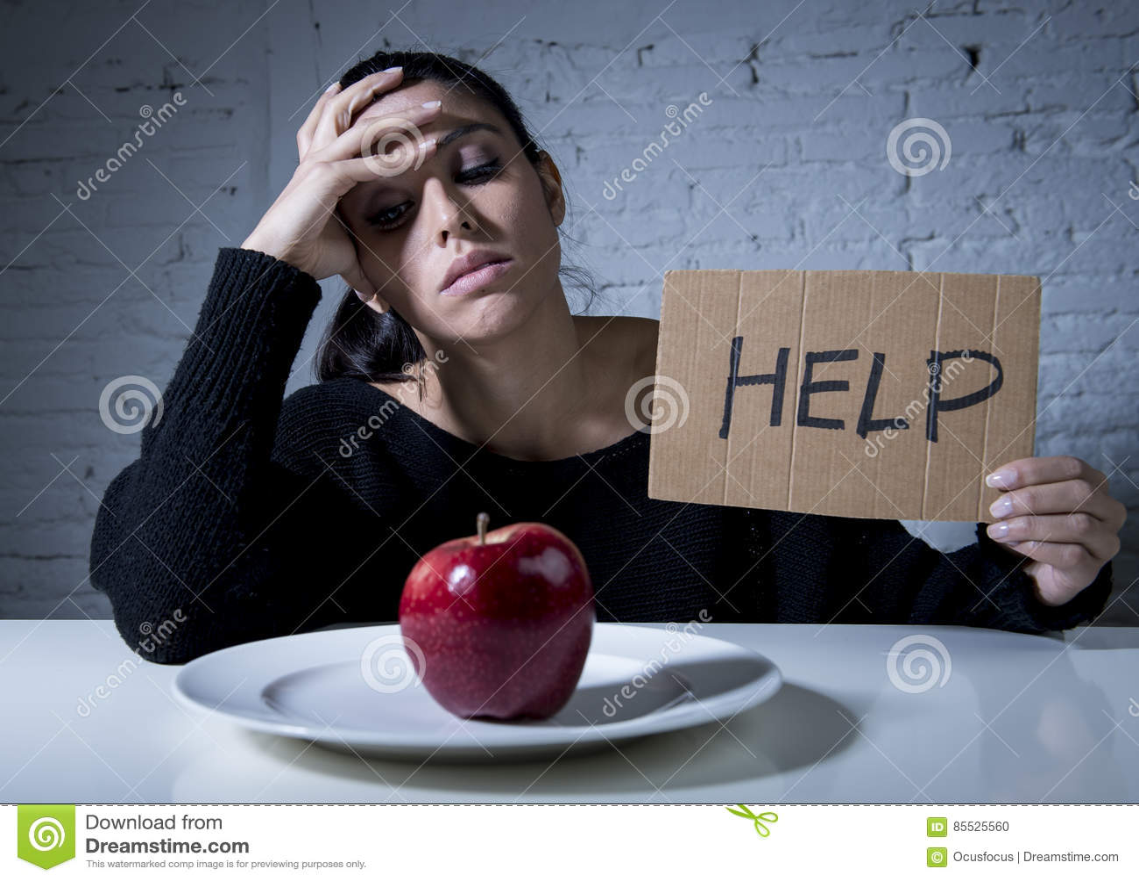 Młoda kobieta lub nastoletnia przyglądająca jabłczana owoc na naczyniu jako symbol szalona dieta w odżywianie nieładzie