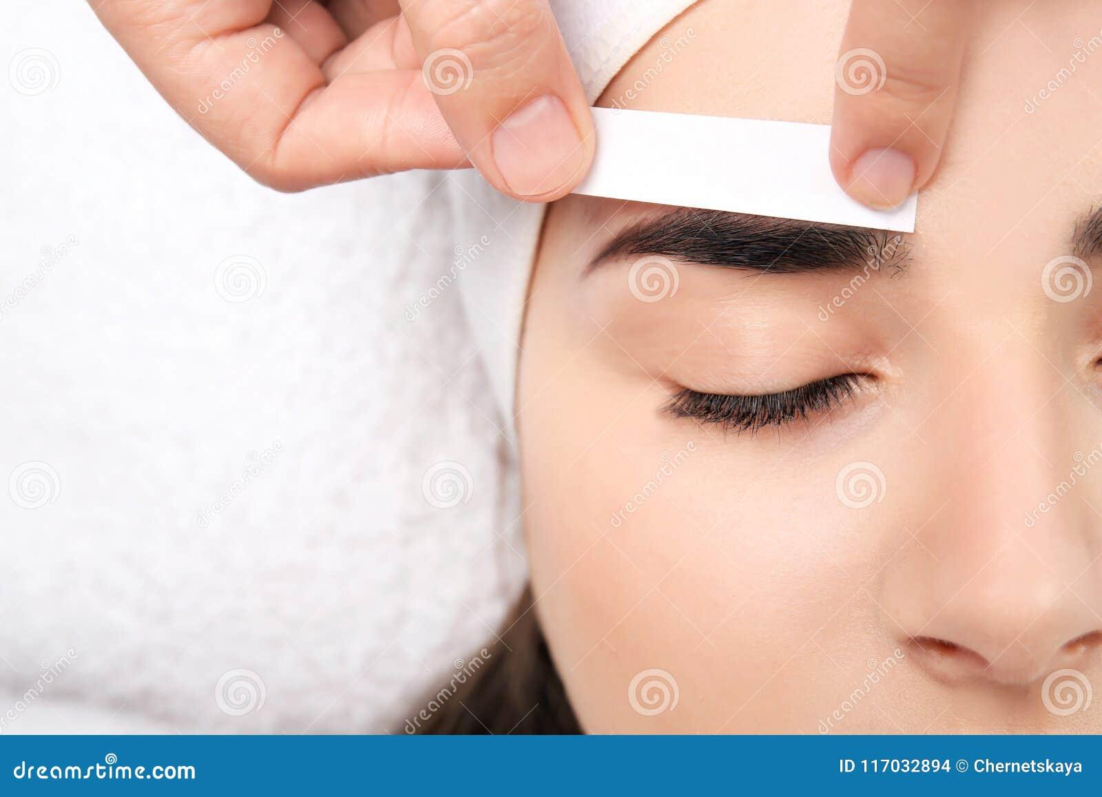 Młoda kobieta ma fachową brwi korekcję