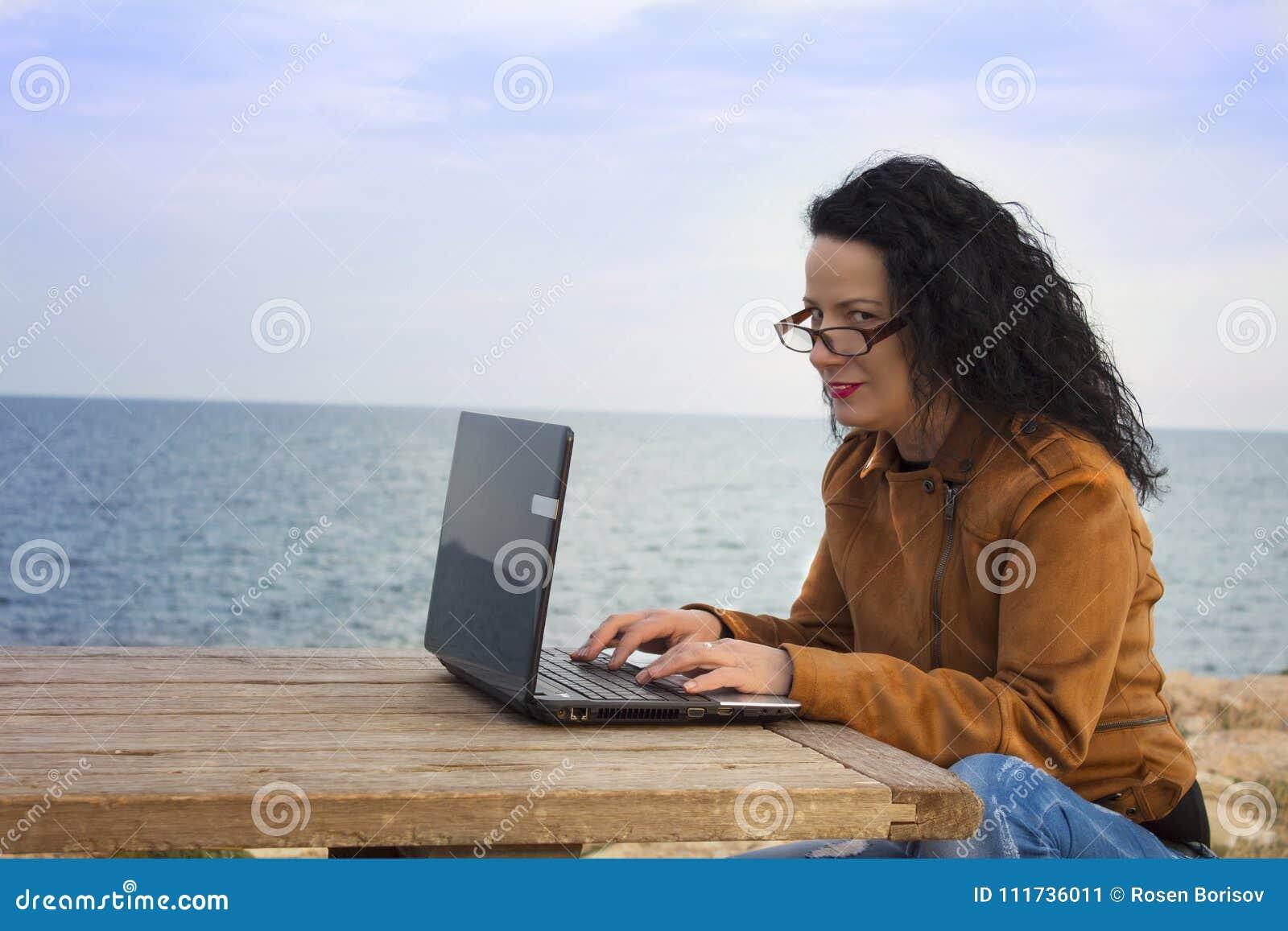 Młoda kobieta na brzeg z komputerem