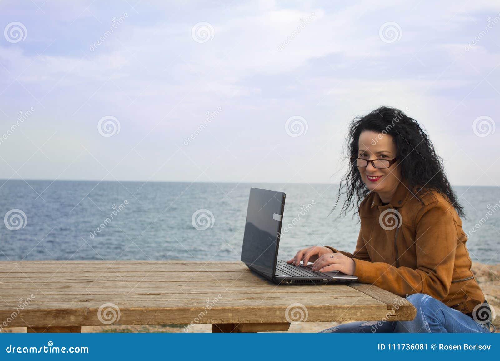 Młoda kobieta na brzeg z komputerem 2
