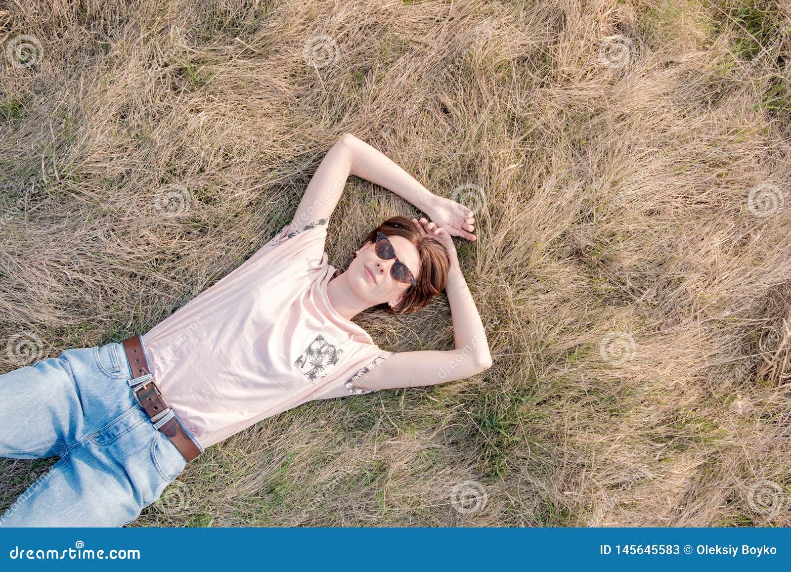 Młoda kobieta na trawie docenia wiosnę