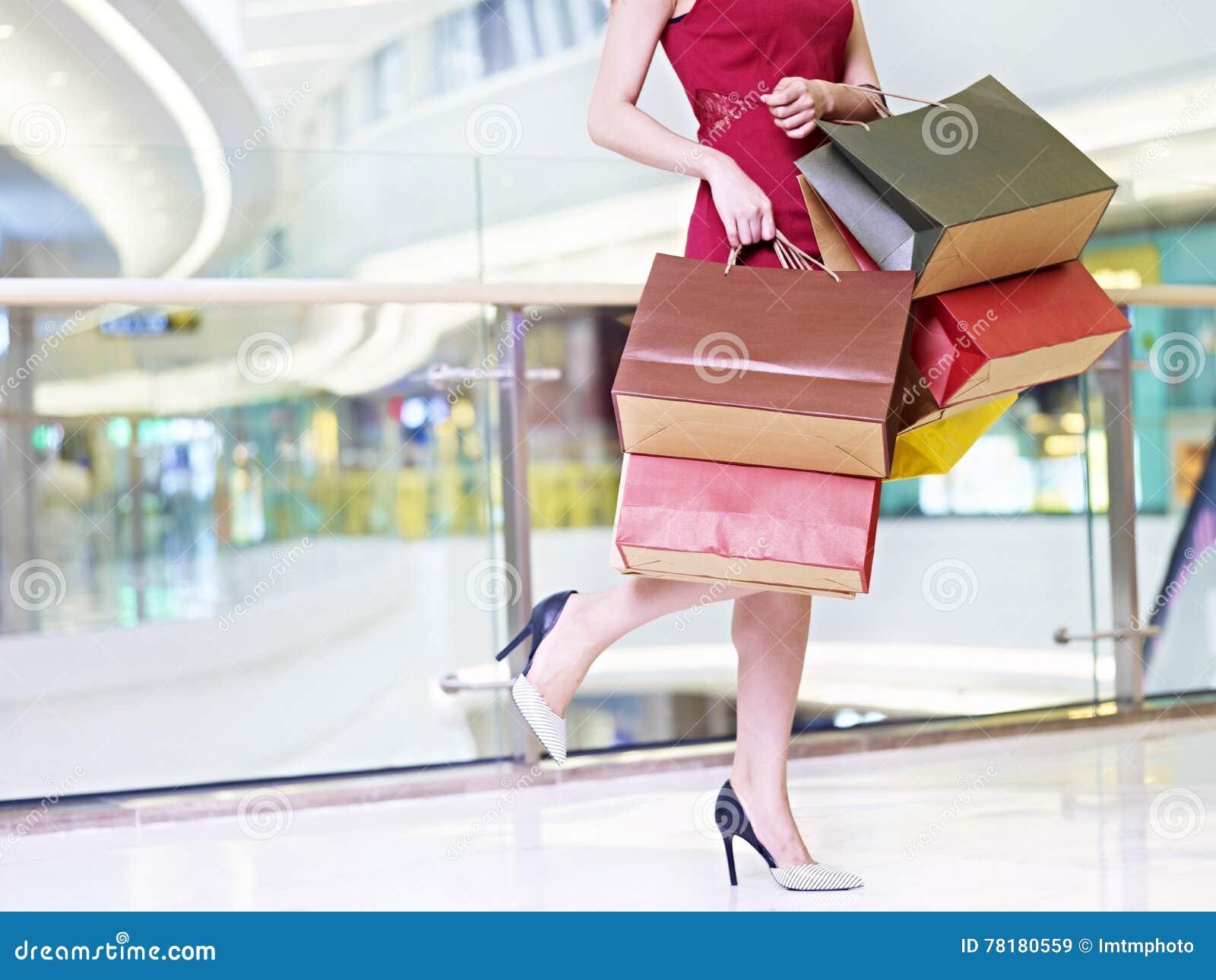 Młoda kobieta niesie kolorowe papierowe torby chodzi w robić zakupy mal