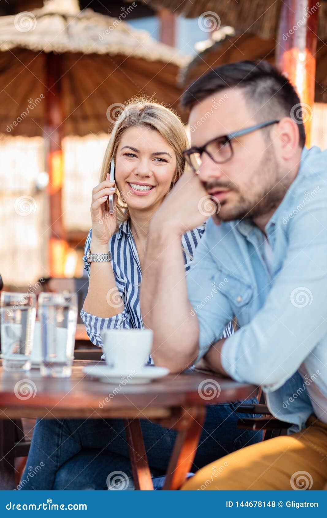 Młoda kobieta opowiada na telefonie i patrzeje jej chłopaka który zanudza i dokucza