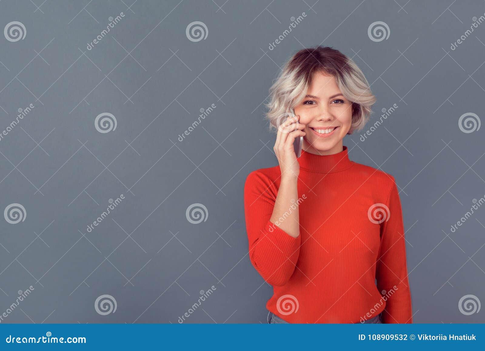 Młoda kobieta opowiada w czerwonej bluzce odizolowywającej na popielatej ścianie telefonem