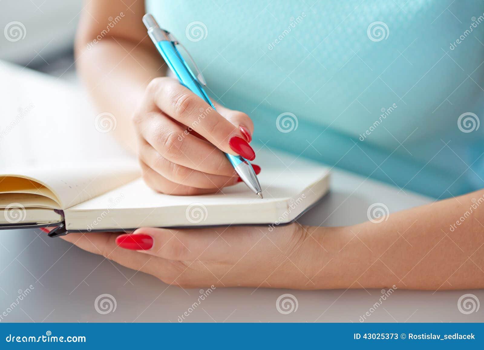 Młoda kobieta pisze czarny dzienniczek