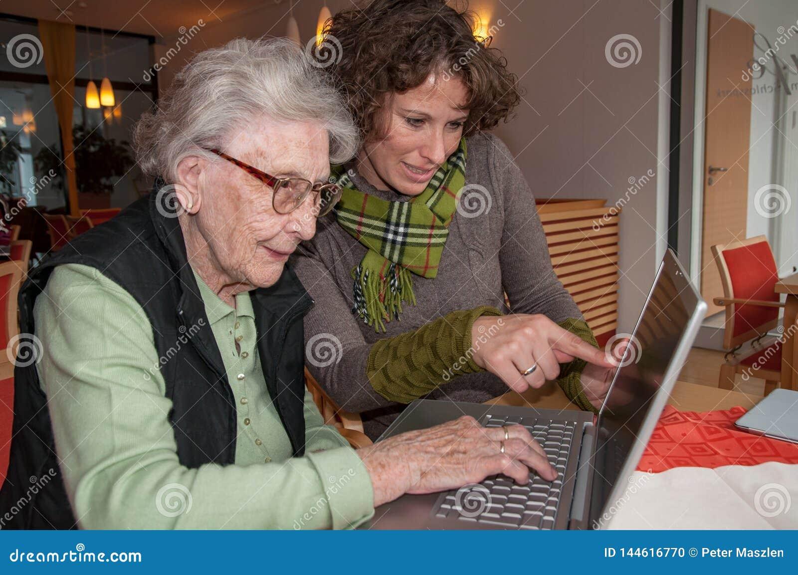 Młoda kobieta pomaga starszej kobiety pracuje z laptopem