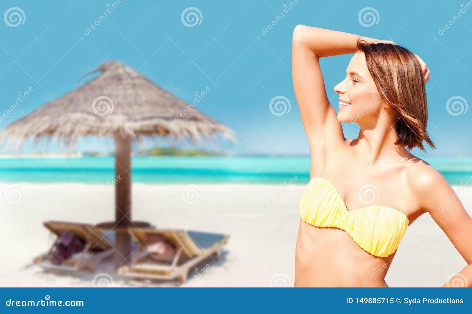 Młoda kobieta pozuje w bikini na plaży