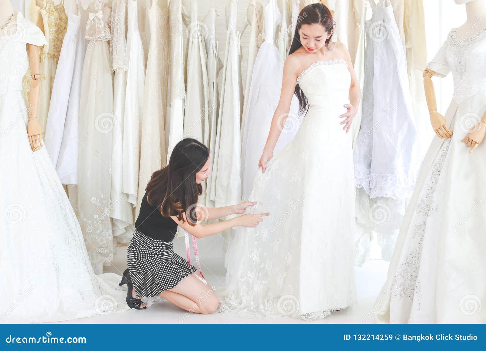 Młoda kobieta próbuje ślubną suknię w studiu, projektant jest jak