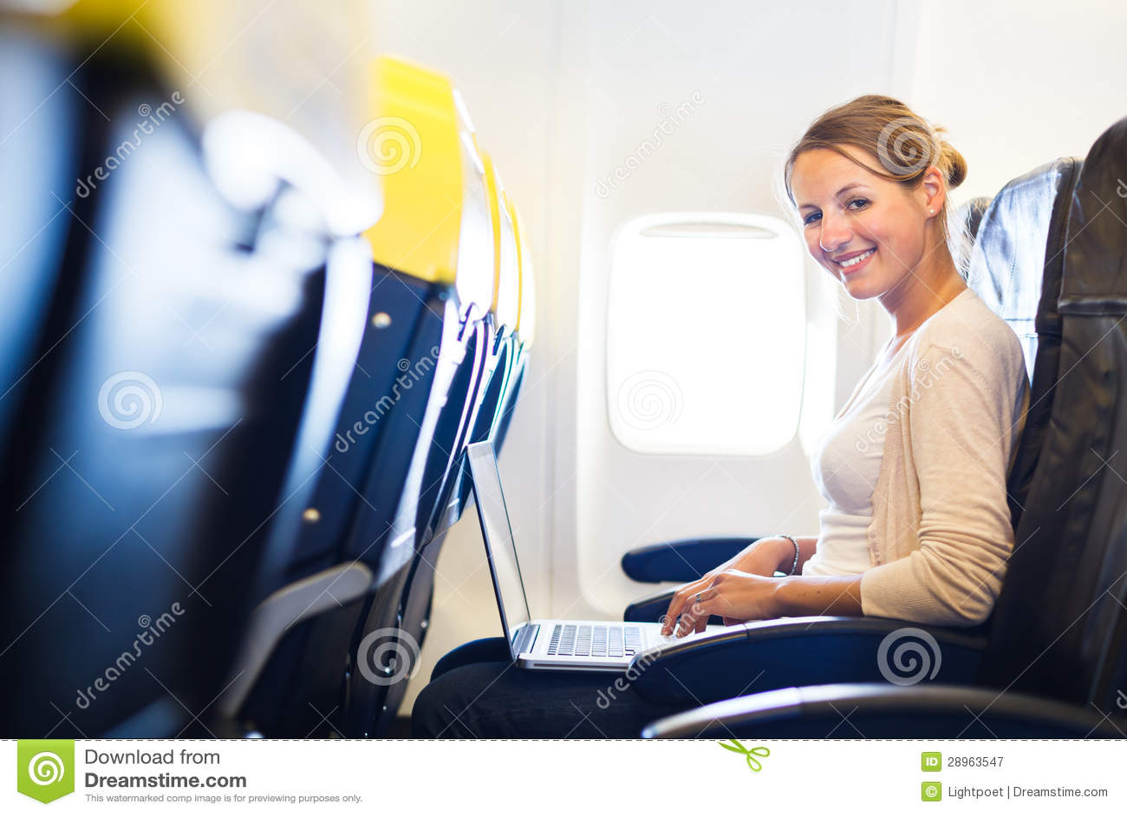 Młoda kobieta pracuje na jej laptopie na pokładzie samolotu