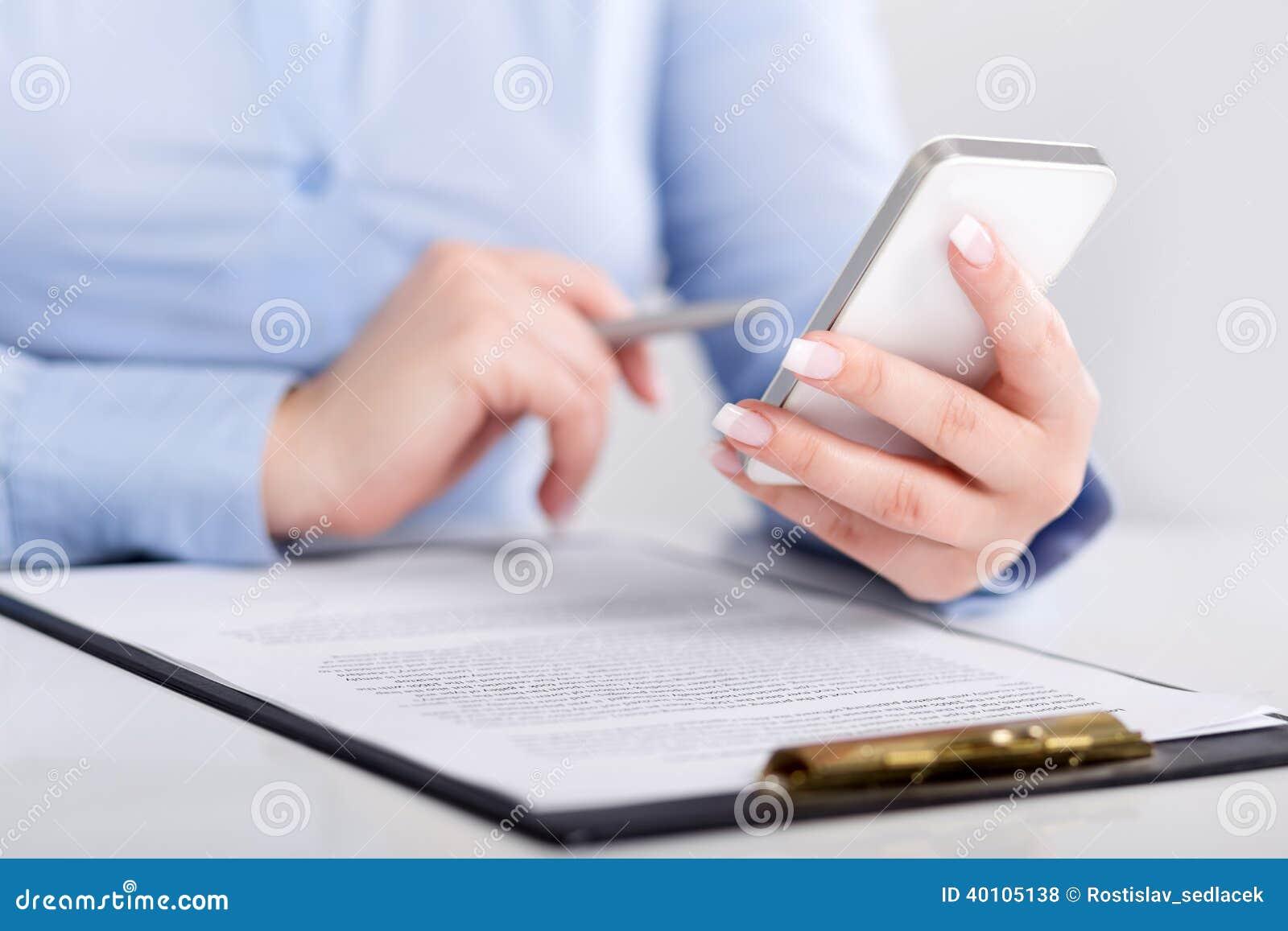 Młoda kobieta pracuje z telefonem komórkowym i trzyma pióro